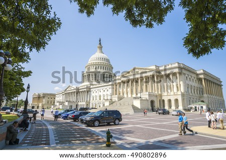 WASHINGTON DC - JULY 30, 2014: Business people and tourists gather near the US Capitol building on a bright summer day.