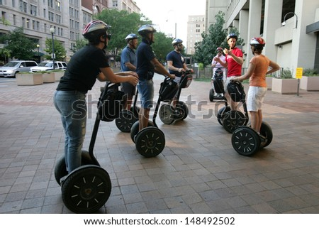 WASHINGTON, DC - JULY 29: Tourists stand on Segways as they listen to a guide during a Segway tour outside the J. Edgar Hoover, FBI headquarters building on July 29, 2013 in Washington.  - stock photo