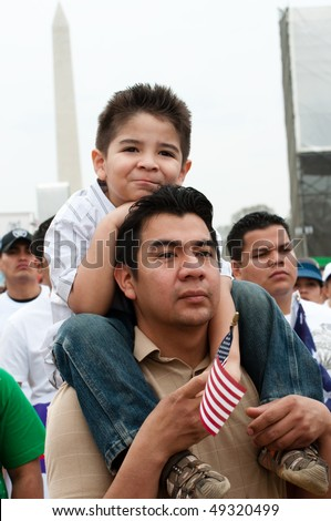 WASHINGTON, DC - MARCH 21: A boy on his father's shoulders stands with some 200,000 immigrants' rights activists flood the National Mall to demand comprehensive immigration reform on March 21, 2010 in Washington DC. - stock photo