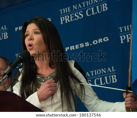WASHINGTON, DC - MARCH 5, 2014:  Ukrainian pop singer and democracy activist Ruslana Lyzhychko sings the Ukrainian National Anthem at the end of her press conference at the National Press Club - stock photo