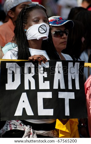 "WASHINGTON, DC - MAY 1: An immigration reform activist holds a sign reading ""Dream Act"" during a protest at the White House on May 1, 2010 in Washington, DC. - stock photo"