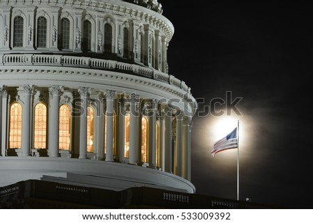 Washington DC - United States Capitol Building dome detail with flapping National Flag on full moon background at night