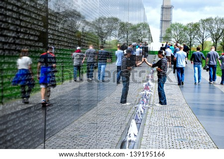 WASHINGTON DC, USA � APR 13 � A young guy is looking up Veterans  names on Vietnam Veterans Memorial wall, Washington Mall, Washington DC, USA. Apr 13, 2013. - stock photo
