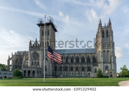 Washington, DC / USA - May 21, 2018: A flag stands at half staff in front of Washington National Cathedral in the wake of the latest school shooting.