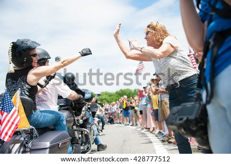 WASHINGTON MAY 29: A bystander shows support to a participant in Rolling Thunder, a motorcycle rally to bring attention to POWs and MIAs of US-involved wars, on May 29, 2016 in Washington, DC.   - stock photo