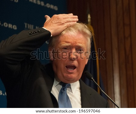 WASHINGTON - MAY 27, 2014 - Real estate mogul Donald Trump demonstrates that the hair on his head really is his, at a National Press Club luncheon. - stock photo