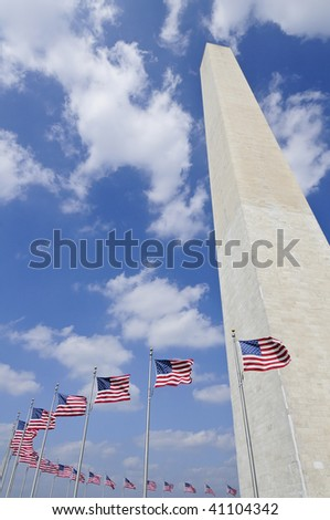 washington monument in Washington DC against blue sky with american flags circling it - stock photo