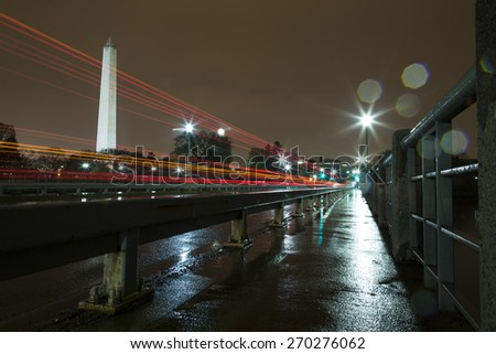 Washington Monument Lit Up at Night in the Rain with Light Trails from Cars. The photo was taken from the Tidal Basin Bridge, showing the reflection of the lights on the sidewalk and pavement. - stock photo