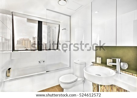 Washroom near glass windows with tiles, wash area and toilet decorated using a light, ceramic bottles with soap on counter top close to white washstand, the mirror is colorful and clean.
