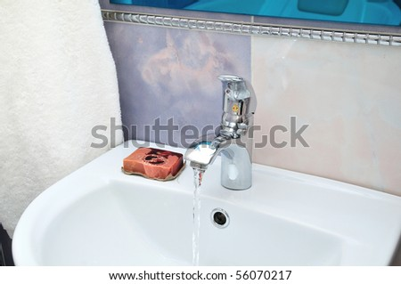 washstand with flowing water soap and towel - stock photo