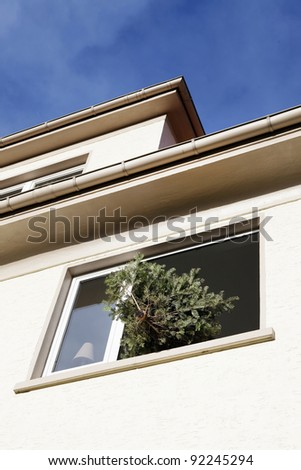 Waste christmas tree out the window of an apartment building - stock photo