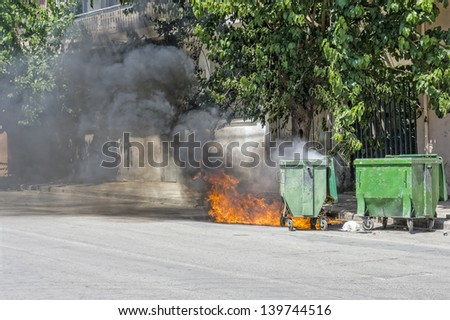 Waste container on wheels, set on fire, emitting smoke - stock photo