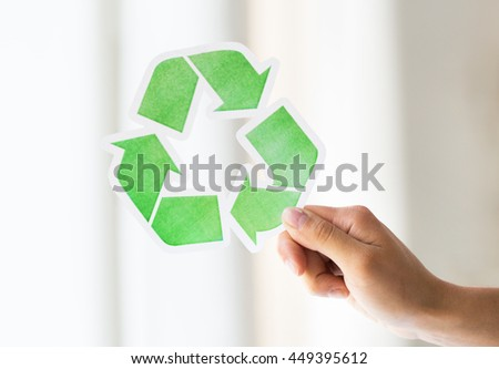 waste recycling, reuse, garbage disposal, environment and ecology concept - close up of hand holding green recycle symbol - stock photo