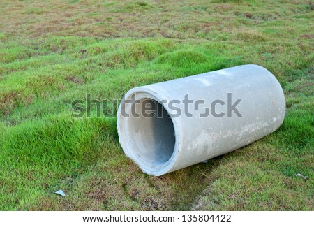 Waste water drain pipe on grass meadow - stock photo