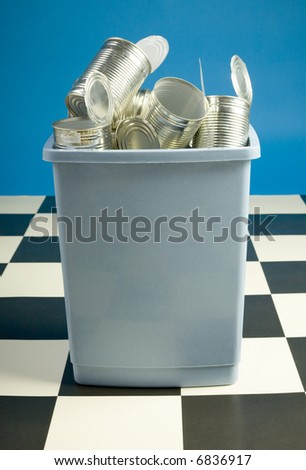 Wastebasket filled with tins standing on floor. Front view - stock photo
