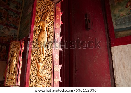 Wat Aham Outama Thany main temple wooden door the ancient Laos art in golden and red tone craving with delicate details, Wat Aham Outama Thany locate at Luang Prabang, Loas