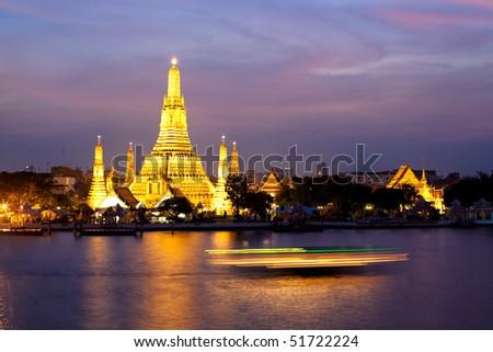 Wat Arun glowing in the pink twilight by Chao Phraya River, Bangkok, Thailand - stock photo