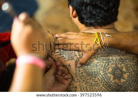 WAT BANG PHRA, THAILAND - MAR 18, 2016: Unidentified monk makes traditional Yantra tattooing during Wai Kroo Master Day Ceremony in Bang Pra monastery, about 50 km west of Bangkok. - stock photo