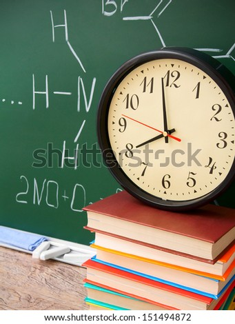 Watch and books against a school board (chemical formulas). - stock photo