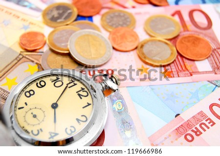 Watch and coins on the euro banknotes. - stock photo
