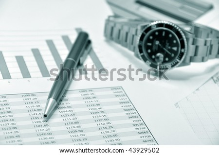 Watch and pen on a market report