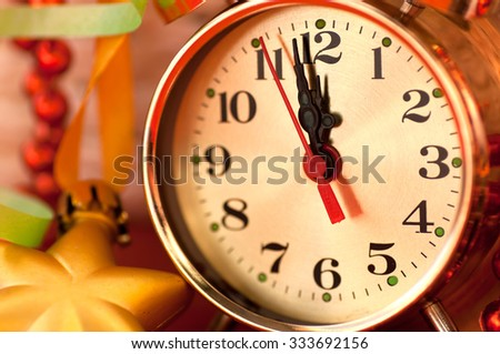 watch hands by 12 hours and Christmas toys background closeup - stock photo