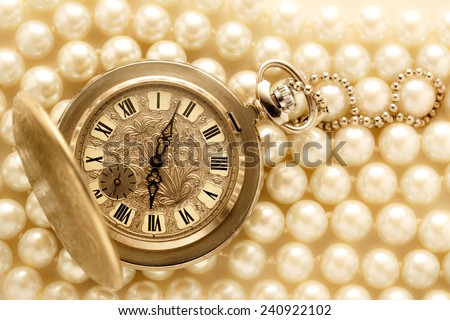 Watch in closeup on pearl background in warm colour  - stock photo