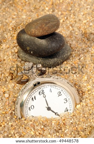 watch in the sand and stones pyramid. time concept - stock photo