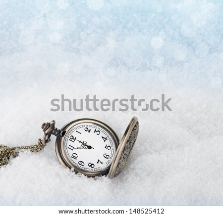 Watch lying in the snow before the new year - stock photo