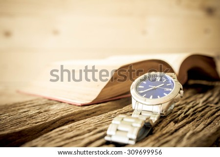 Watch with open book on old wooden table, vintage style. - stock photo