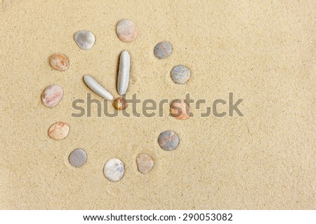 Watch with stones laid on the sand as a background - stock photo