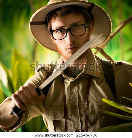 Watchful young adventurer holding a machete walking through the jungle. - stock photo