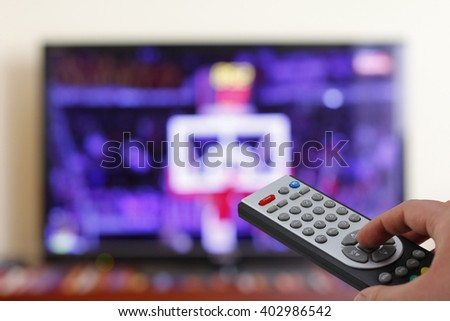 Watching a basketball match in the television, with a tv remote control in the hand
