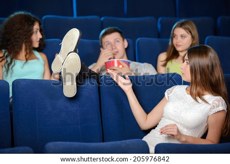 Watching a movie. Young men holding his feet on the seat while watching movie at cinema - stock photo