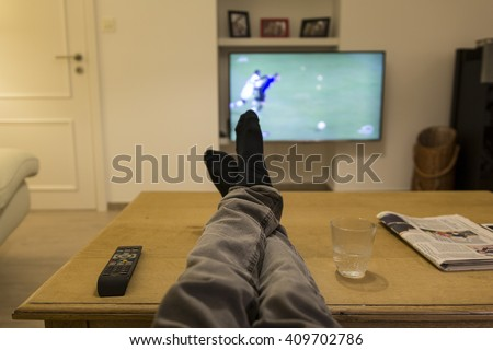 Watching a soccer match on TV with the feet on the table. - stock photo
