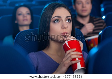 Watching an exciting movie. Attractive young woman drinking soda while watching movie at the cinema  - stock photo