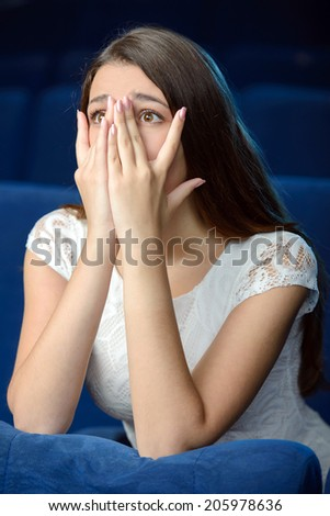 Watching horror movie. Side view of terrified young women covering her face with hand while watching movie at the cinema - stock photo