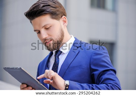 Watching news. Vivacious bearded businessman keeping glance down and holding laptop while surfing the Internet.