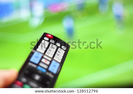 Watching soccer game on modern tv, with a close-up of the remote control - stock photo