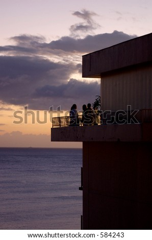 watching sunset from balcony - stock photo