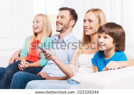 Watching their favorite show. Side View of happy family of four bonding to each other and smiling while watching TV at home together  - stock photo