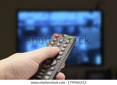 Watching TV and using remote controller  - stock photo