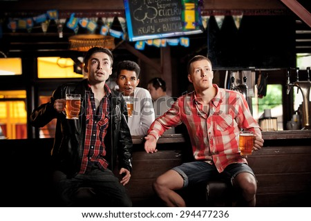 Watching TV in bar. happy young men drinking beer and gesturing while sitting in bar - stock photo