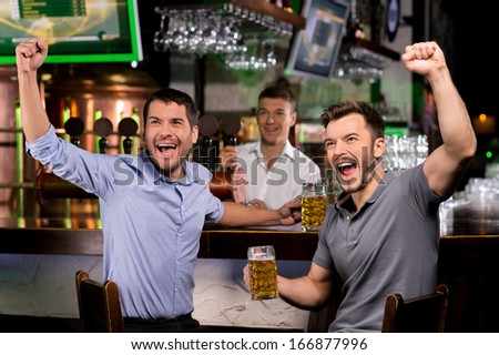 Watching TV in bar. Two happy young men drinking beer and gesturing while sitting in bar - stock photo