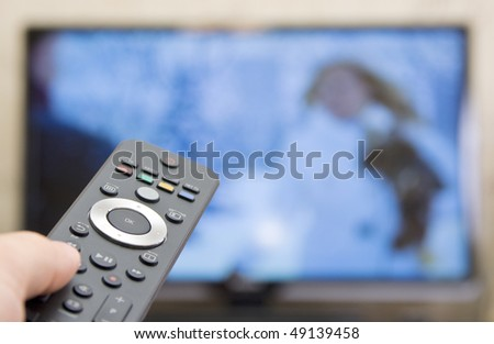 Watching TV. Remote control with blured TV on background - stock photo
