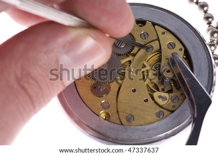 Watchmaker or repair man in action, repairing old watch with tweezers and precision screwdriver - stock photo