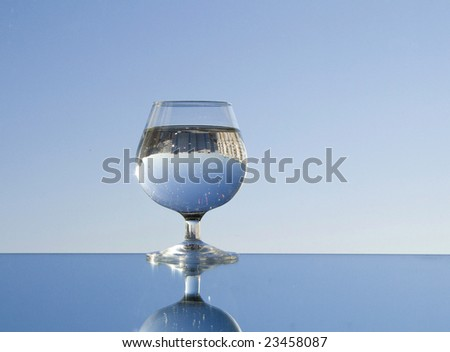 Water and glass reflected in a mirror on blue sky background. Pure water concept