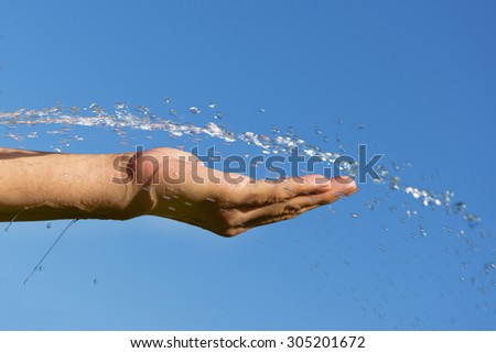 Water and hand against blue sky.