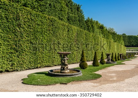Water Avenue in beautiful gardens of famous Versailles palace. The Palace of Versailles was a royal chateau. It was added to the UNESCO list of World Heritage Sites. Paris, France. - stock photo