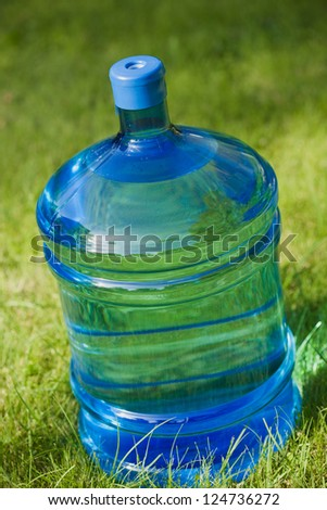 water big bottle on green grass background - stock photo